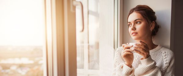 Solemn woman drinking tea by the window